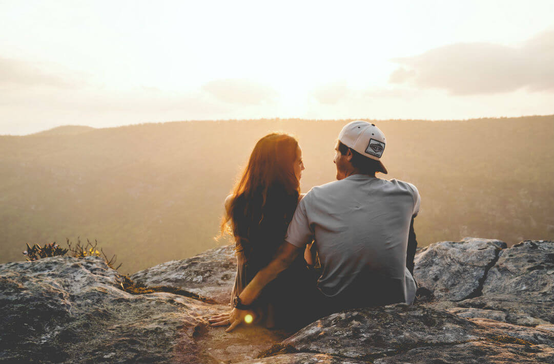 couple sitting together on mountain top