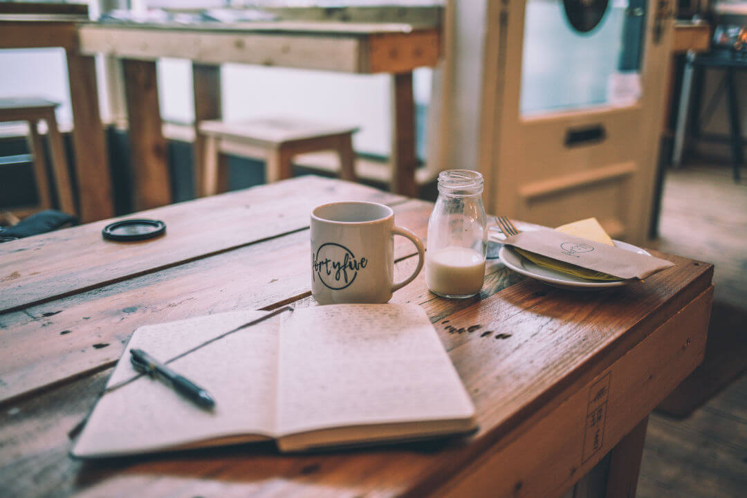 open notebook and a cup of coffee