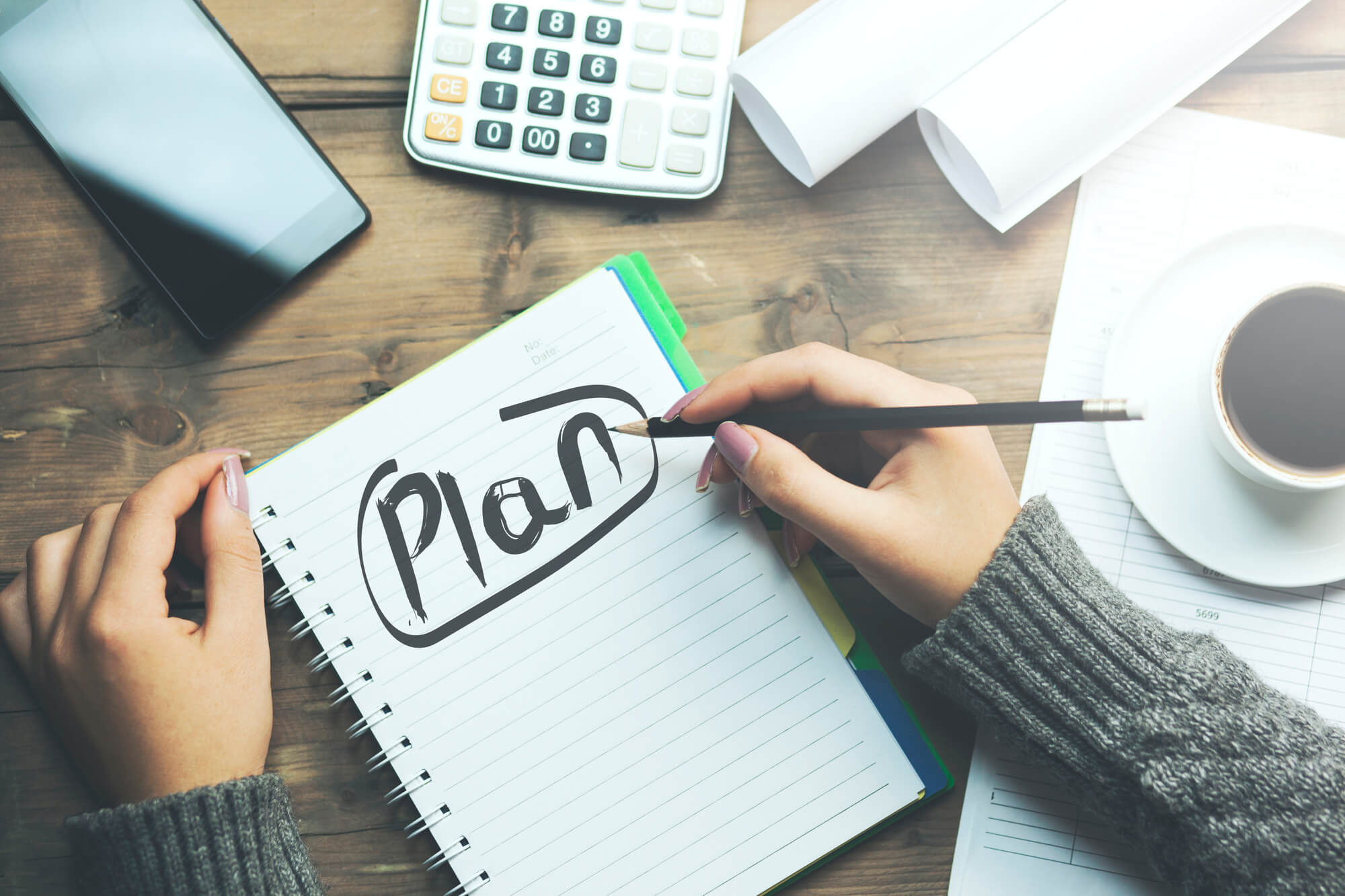 "woman writing ""Plan"" in notebook"