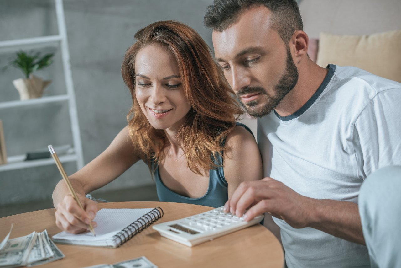 adult couple sitting with calculator and notepad