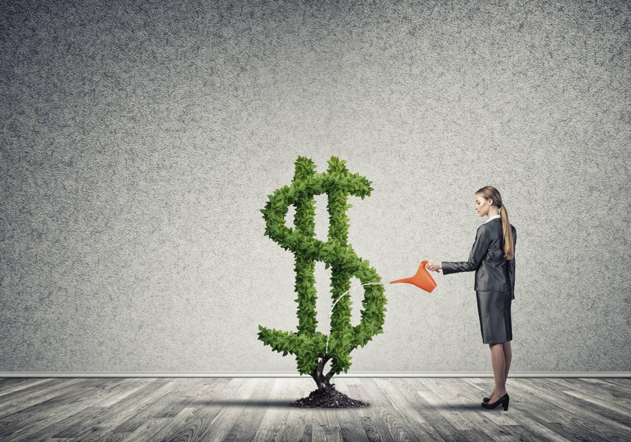 woman watering dollar sign shaped shrub